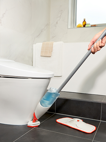 cleaning around the toilet with a spray mop
