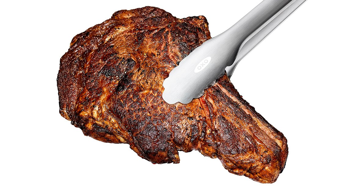 perfecly cooked steak in tongs