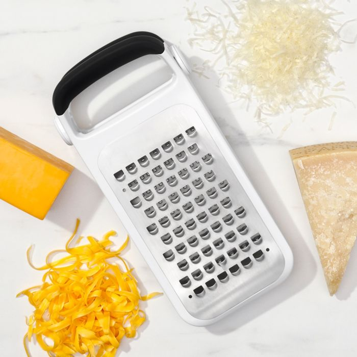 OXO Good Grips Etched Two-Fold Grater surrounded by grated cheese