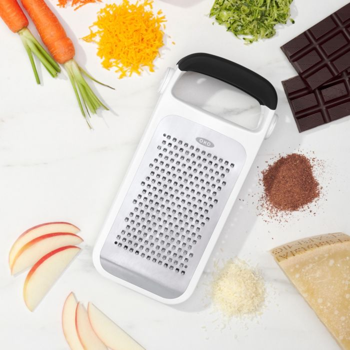 OXO Good Grips Etched Two-Fold Grater surrounded by grated foods