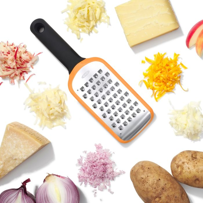 OXO Good Grips Etched Coarse Grater surrounded by shredded food
