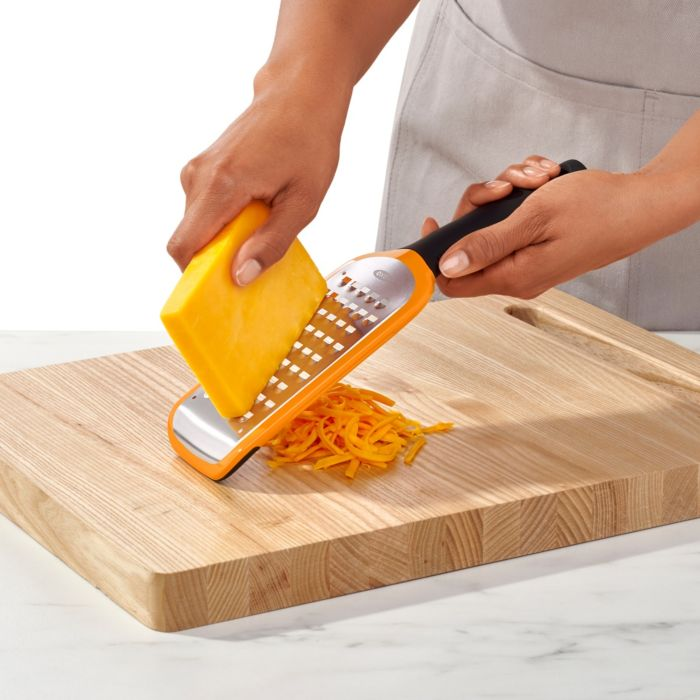 Person grating cheese on OXO Good Grips Etched Coarse Grater