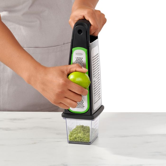 Person zesting lime with zest going into integrated food container of Etched Box Grater With Removable Zester