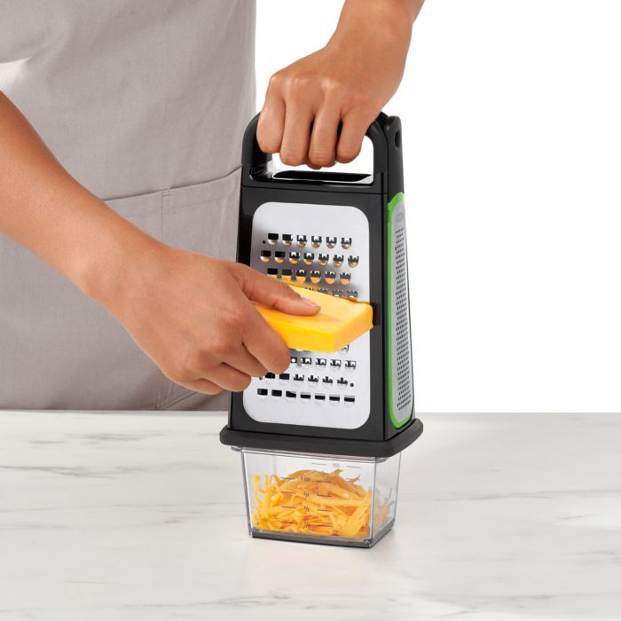 Person grating cheese with Etched Box Grater and shavings going into integrated food container