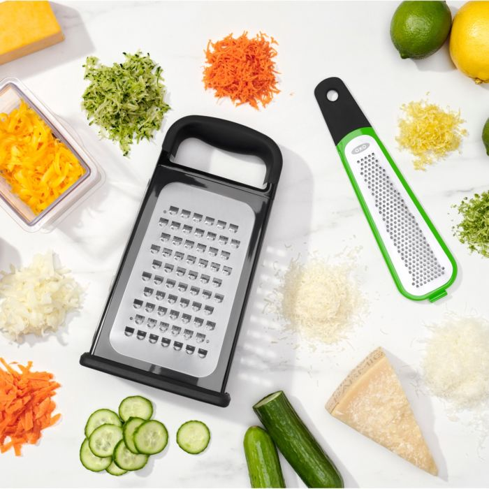 Etched Box Grater With Removable Zester surrounded by grated food