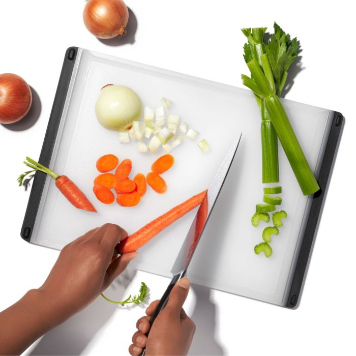 Person chopping carrots on OXO Good Grips Utility Cutting Board
