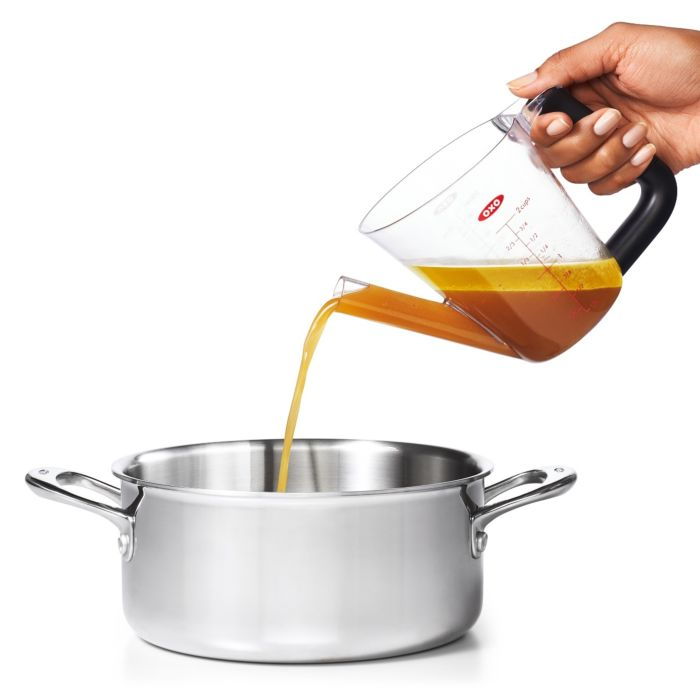 person pouring gravy from OXO Good Grips 2 Cup Fat Separator with lid off