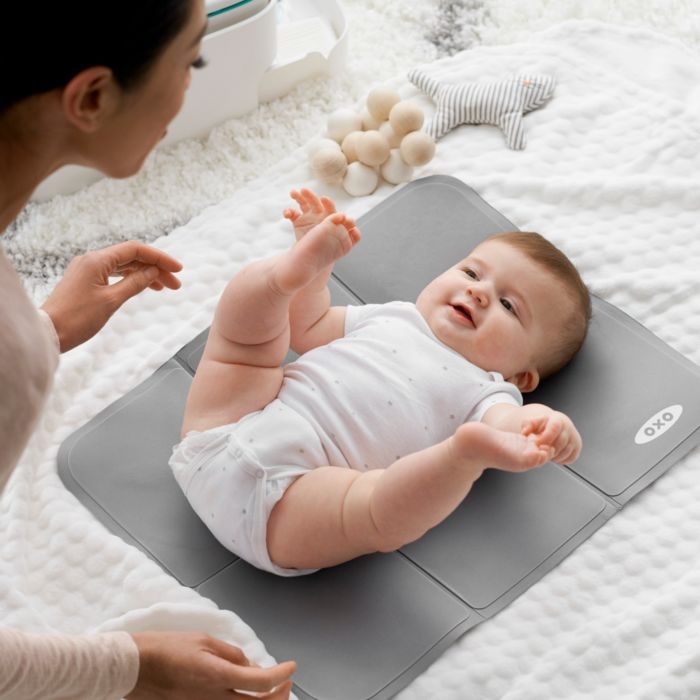 Baby on changing mat from OXO Tot Diaper Caddy with Changing Mat