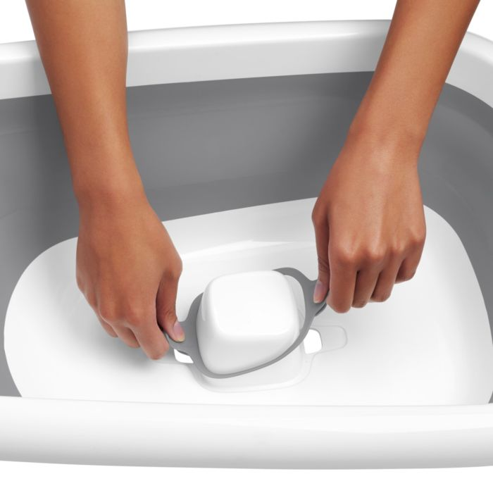 Person pulling out tabs of easy-to-access dual-sided drain in OXO Tot Splash & Store Bathtub