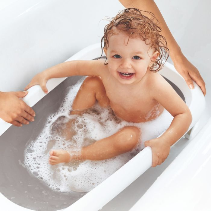 Parent bathing toddler in OXO Tot Splash & Store Bath Tub